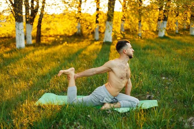 Uomo a praticare yoga in un parco al tramonto bellissimo. uno stile di vita sano