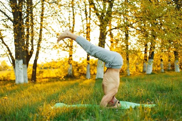 Uomo a praticare yoga nel parco sull'erba al tramonto, uno stile di vita sano