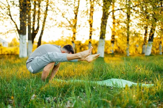 Uomo a praticare yoga nel parco al tramonto. uno stile di vita sano
