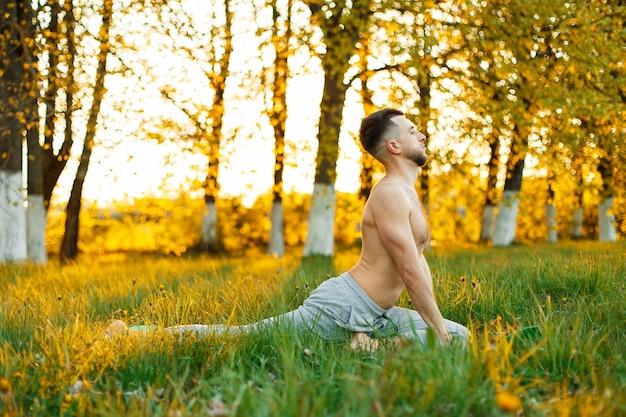Uomo a praticare yoga al tramonto. uno stile di vita sano
