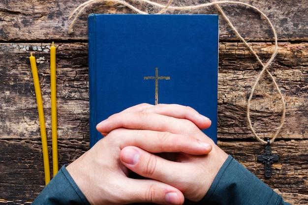 Uomo che prega sulla bibbia