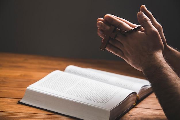 Un uomo che prega su un libro su una superficie scura
