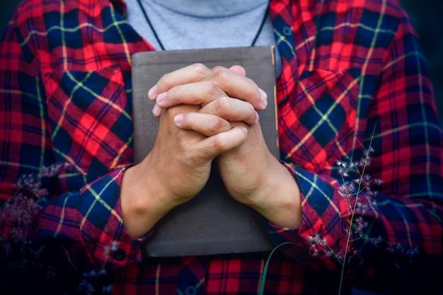 Un uomo che prega tenendo una sacra bibbia. concetto cristiano.
