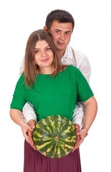 Un uomo e una donna incinta tengono in mano un grosso cocomero. isolato su sfondo bianco.