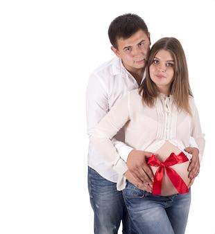Un uomo e una donna incinta in jeans e camicia bianca. nastro rosso legato intorno alla pancia di una donna incinta su sfondo bianco