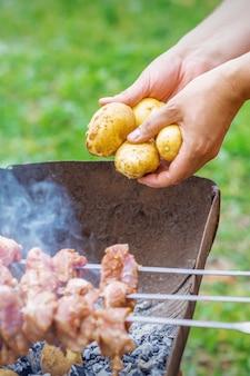 L'uomo prepara la carne barbecue con patate
