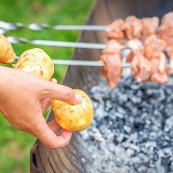 L'uomo prepara la carne al barbecue con le patate