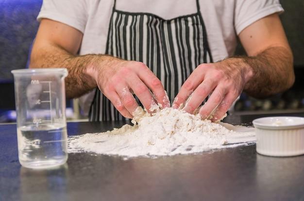 Uomo che prepara la pasta della pizza sulla tavola di granito nero