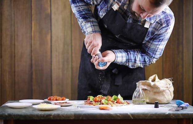 Un uomo che prepara una pizza, impasta l'impasto e mette gli ingredienti