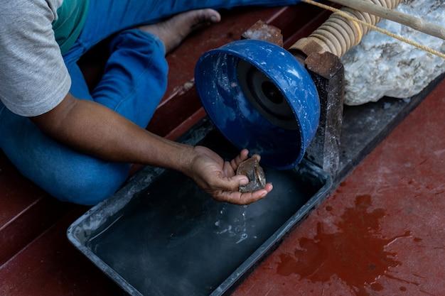 Un uomo lavora una pietra su una macchina portatile antique craft