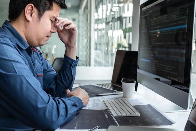 Programmatore uomo stressato e progetto mal di testa nel computer di sviluppo software nell'ufficio dell'azienda it, scrittura di codici e sito web di codici dati e tecnologie di database di codifica per trovare una soluzione.