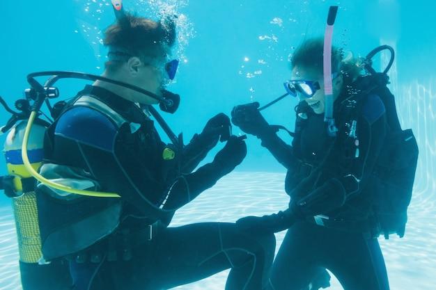 Uomo che propone il matrimonio alla sua fidanzata sconvolta sott'acqua in attrezzatura da sub