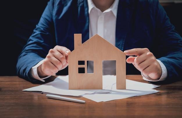 Uomo che propone di firmare una polizza assicurativa immobiliare, l'agente è in possesso del modello di casa in legno. concetto di assicurazione immobiliare.