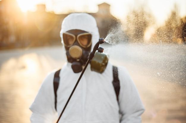 Uomo in equipaggiamento protettivo che disinfetta la città
