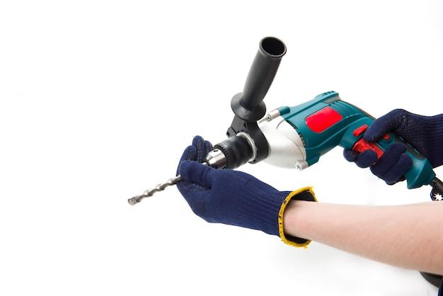 L'uomo in guanti protettivi cambia trapano nel perforatore elettrico