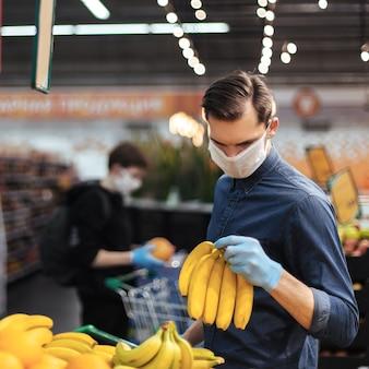 Uomo in guanti protettivi che sceglie le banane in un supermercato