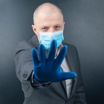 L'uomo in guanti protettivi mostra una maschera facciale medica. epidemia di coronavirus e protezione personale per l'uomo