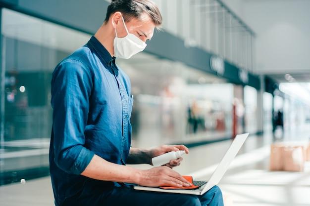 L'uomo in una maschera protettiva disinfetta il suo laptop. pandemia in città