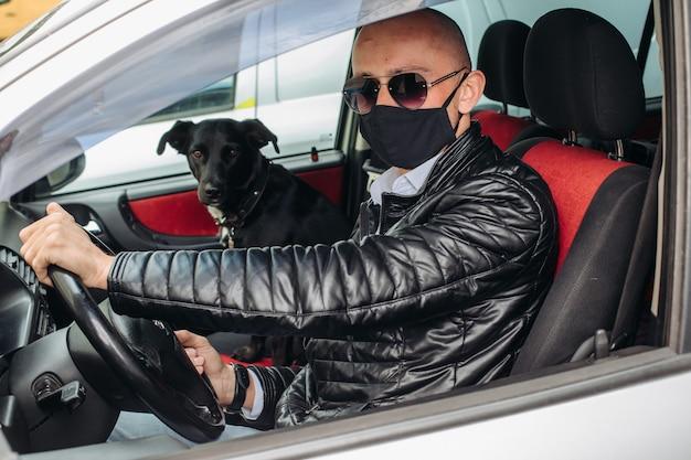 Un uomo con una maschera protettiva alla guida di un'auto. un uomo con una maschera protettiva alla guida di un'auto va in farmacia. un uomo è seduto in macchina e indossa una maschera da coronavirus, mentre un cane è seduto sul sedile anteriore