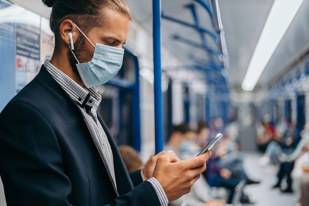 Uomo con una maschera protettiva in piedi in un vagone della metropolitana