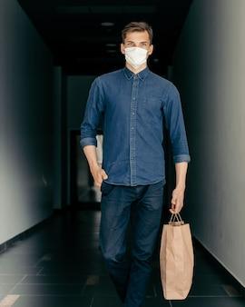 Uomo in una maschera protettiva che cammina lungo una strada cittadina