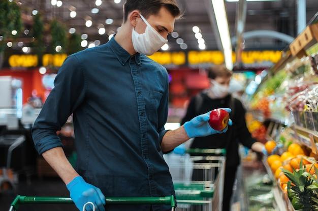 Uomo con una maschera protettiva quando si selezionano le mele al supermercato. igiene e assistenza sanitaria