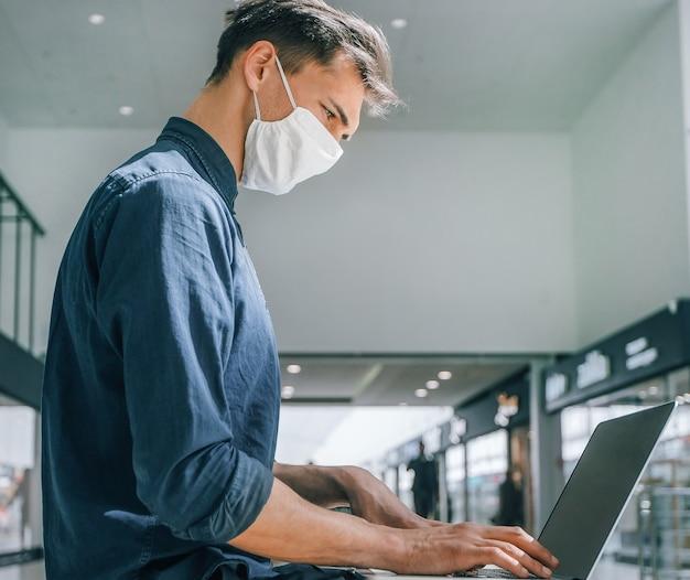 L'uomo con una maschera protettiva lavora su un laptop in un edificio del centro commerciale