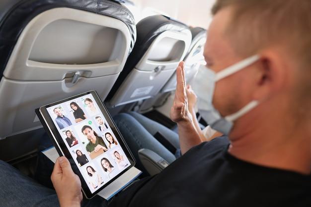 L'uomo con maschera medica protettiva conduce una conferenza online di lavoro a distanza tramite tablet durante il trasporto