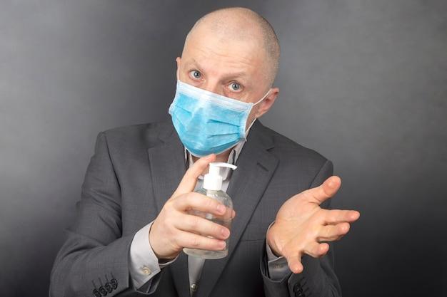 L'uomo in una maschera medica protettiva durante la quarantena disinfetta le mani