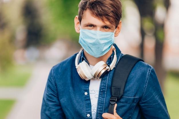 L'uomo in una mascherina medica protettiva sul suo viso cammina attraverso il parco con le cuffie senza fili intorno al collo. quarantena, coronavirus
