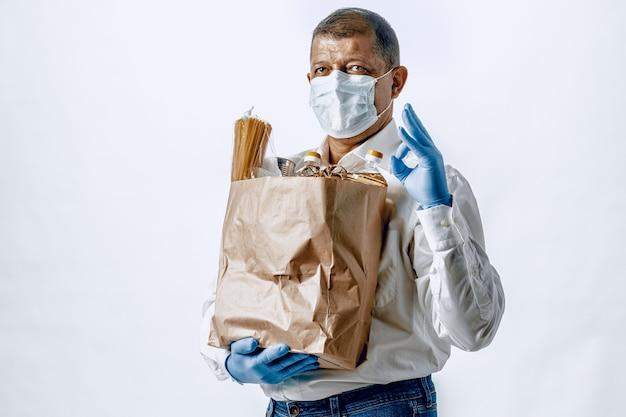 Uomo in una maschera medica protettiva con un sacchetto da un negozio di alimentari. consegna del cibo