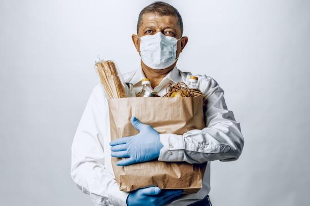 Uomo in una mascherina medica protettiva con una borsa da una drogheria