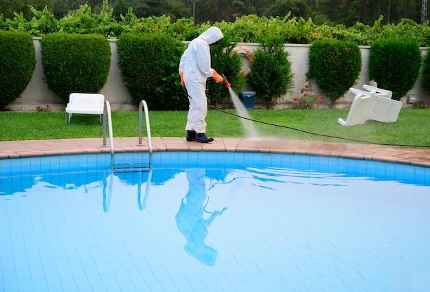 L'uomo in tuta protettiva disinfetta il fondo della piscina