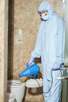 Uomo in tuta protettiva che utilizza prodotti chimici disinfettanti nel wc
