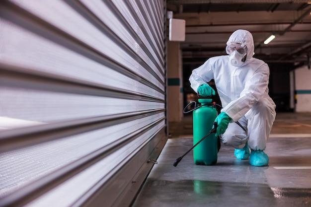 Uomo in uniforme sterile protettiva accovacciato e disinfettante garage con disinfettante