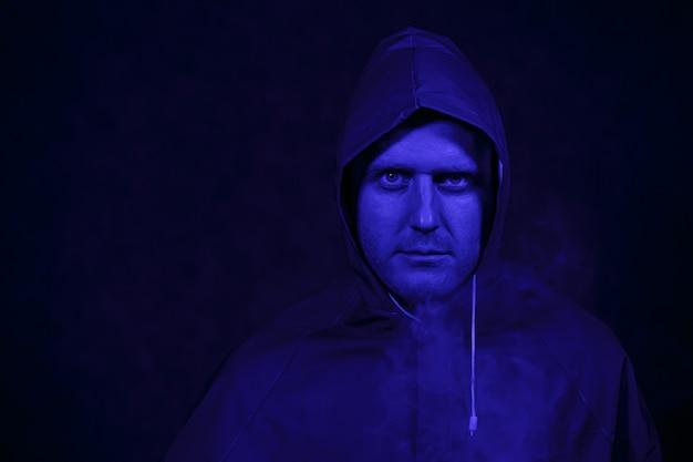 Un uomo con una tuta protettiva in una stanza buia. concetto di immagine di halloween. protezione dal virus. illuminato con luci colorate