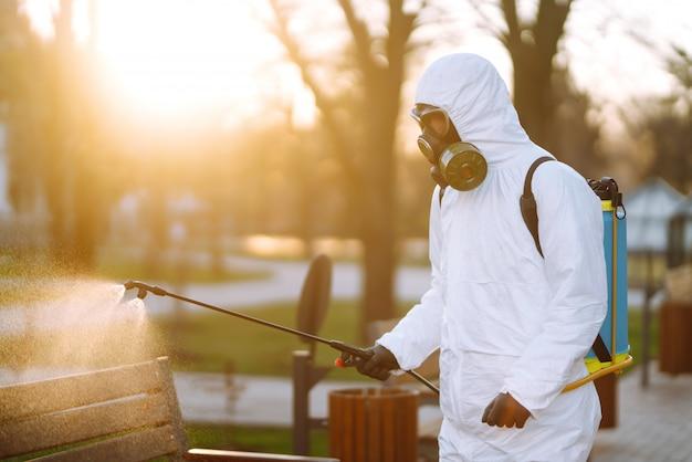 Uomo nel banco di disinfezione del vestito protettivo nel parco pubblico nella città di quarantena. prevenzione delle infezioni e controllo dell'epidemia. covid 19.