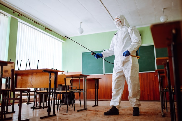 Uomo in una tuta protettiva che disinfetta un'aula