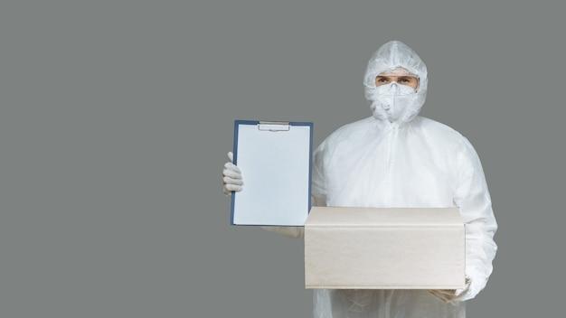 Uomo in una tuta protettiva, guanti e maschera di corriere di consegna della posta l'uomo mostra il lavoro negli appunti per la consegna