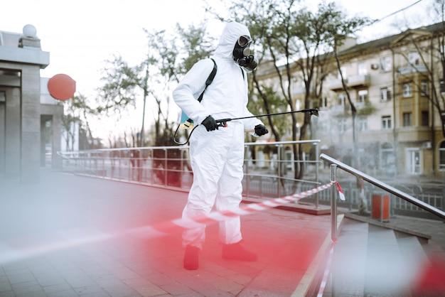 L'uomo in tuta protettiva e maschera spruzza il disinfettante sulla ringhiera nel luogo pubblico vuoto all'alba nella città di quarantena. covid 19. concetto di pulizia.