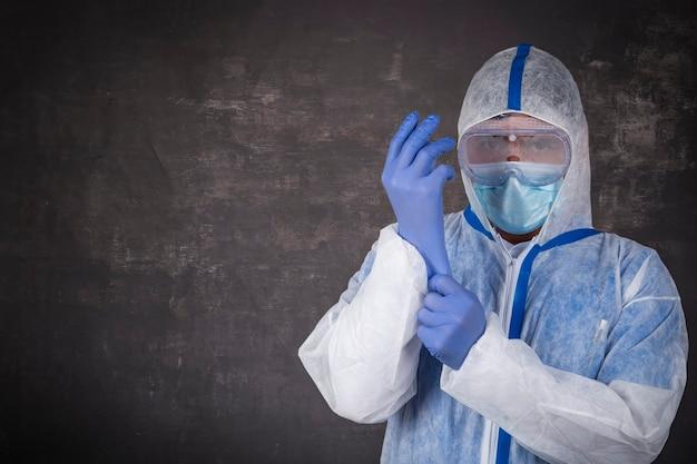 Uomo in tuta protettiva, mascherina chirurgica e guanti in lattice