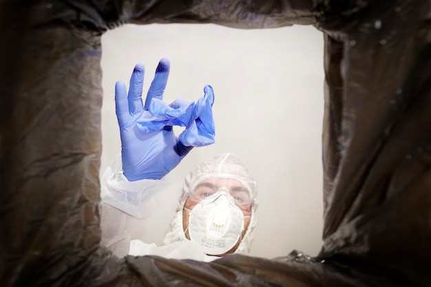 Un uomo con una tuta protettiva getta un guanto medico usato in un bidone della spazzatura. vista dal basso dal cestino. il problema del riciclaggio e dell'inquinamento del pianeta con i rifiuti.