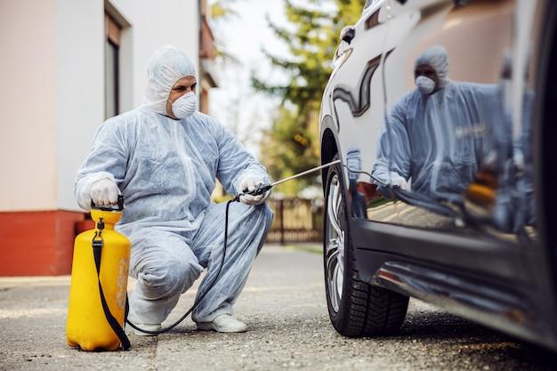 Uomo in tuta protettiva con maschera che disinfetta i pneumatici dell'auto, previene l'infezione da coronavirus, la contaminazione di germi o batteri.