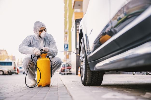 Uomo in tuta protettiva con maschera che disinfetta i pneumatici dell'auto, previene l'infezione da virus del coronavirus covid-19, la contaminazione di germi o batteri. prevenzione delle infezioni e controllo dell'epidemia. protezione su