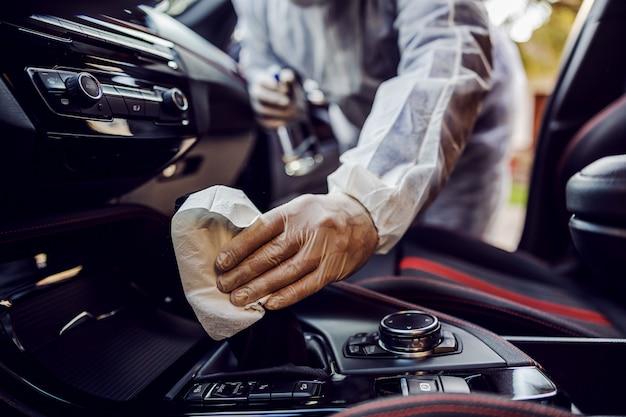 Uomo in tuta protettiva con maschera disinfettante all'interno dell'auto, pulire le superfici che vengono toccate frequentemente, prevenire l'infezione da coronavirus, la contaminazione di germi o batteri. infezione