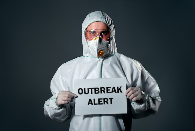 Uomo in tuta bianca protettiva, maschera e occhiali sul viso, con un foglio di carta, con la scritta outbreak alert.