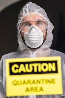 Uomo in tuta bianca protettiva, maschera e occhiali sul viso