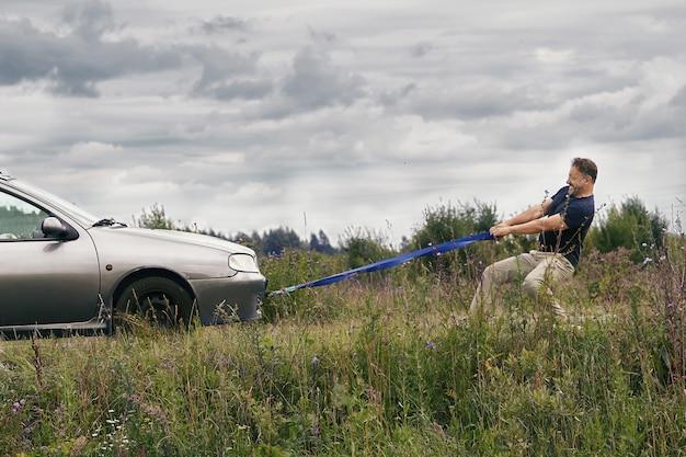 Uomo che tira la sua automobile rotta utilizzando una fune di traino lungo una strada di campagna