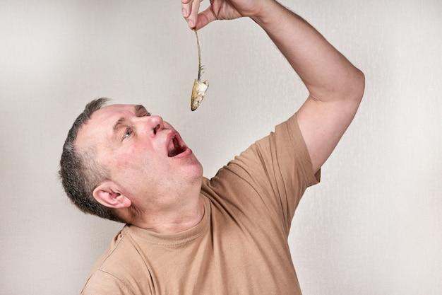 Un uomo tira fuori un pesce puzzolente rosicchiato fino all'osso con la mano