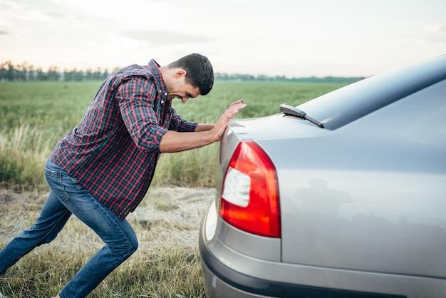 Uomo che spinge auto rotta, vista laterale. veicolo con trounble sul ciglio della strada nel giorno d'estate